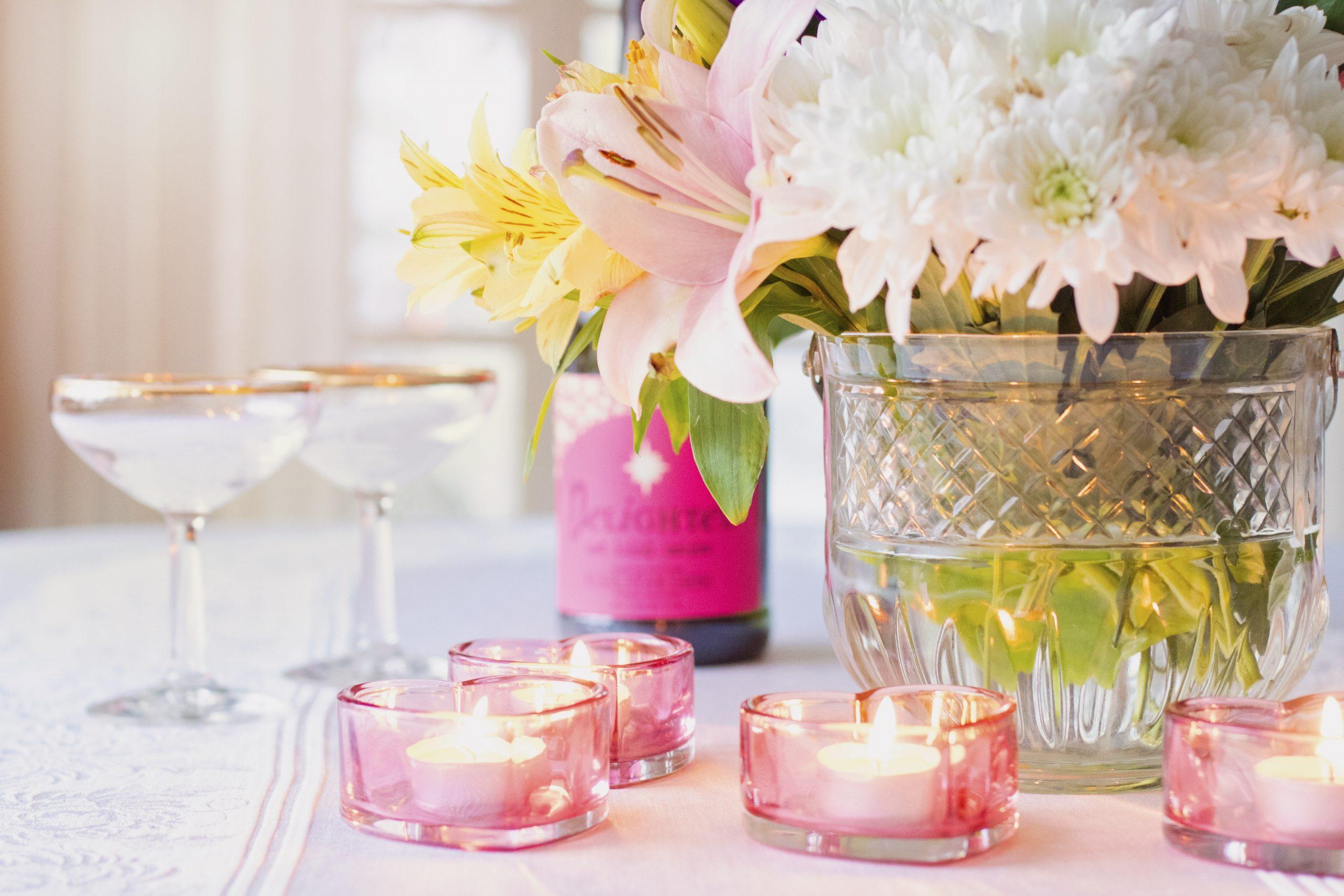 Festlich gedeckter Tisch mit einem Blumenstrauß, zwei Champagnergläsern und rosa Teelichtern.