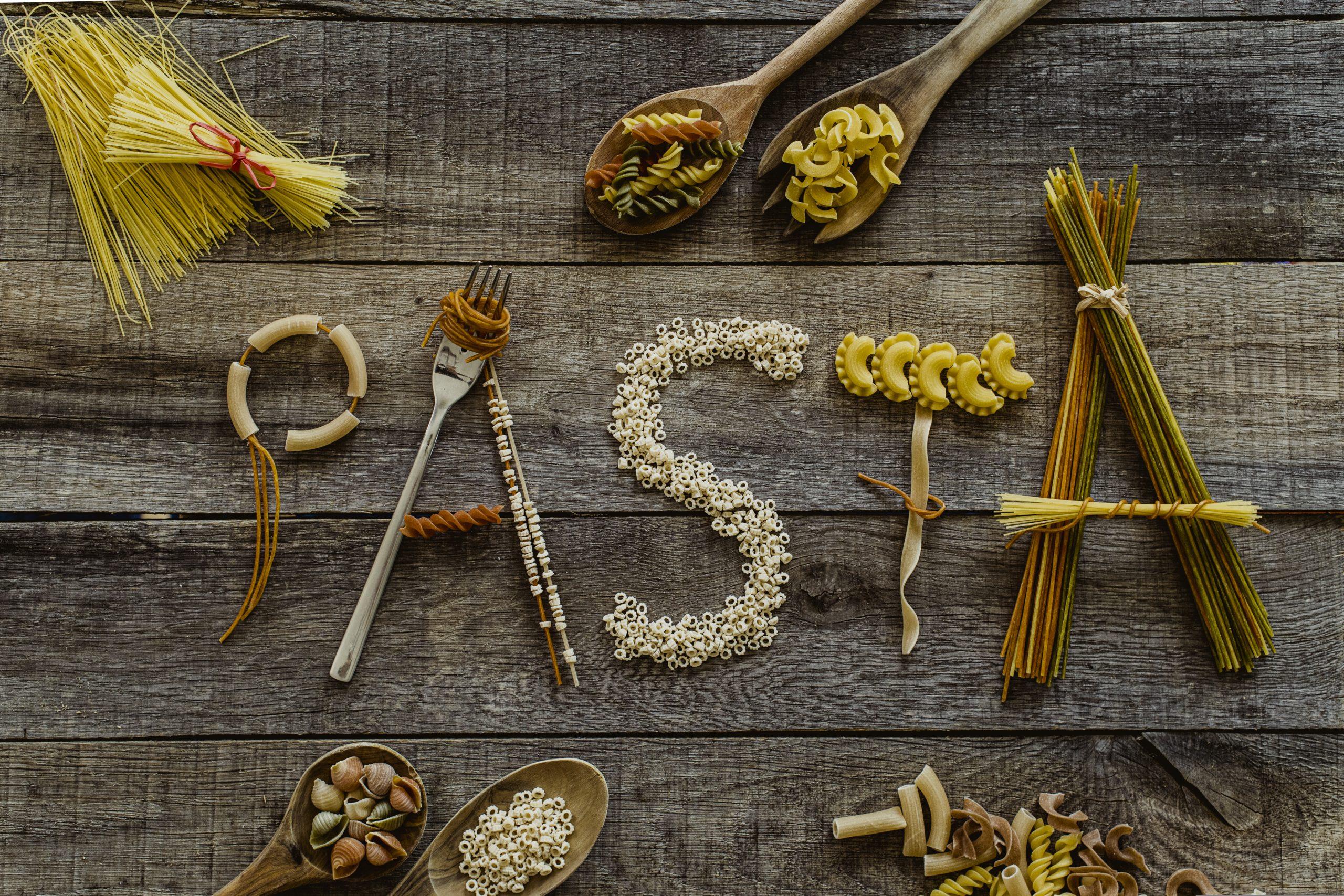 Verschiedenste Nudeln zum Wort Pasta auf einem Holztisch aufgelegt