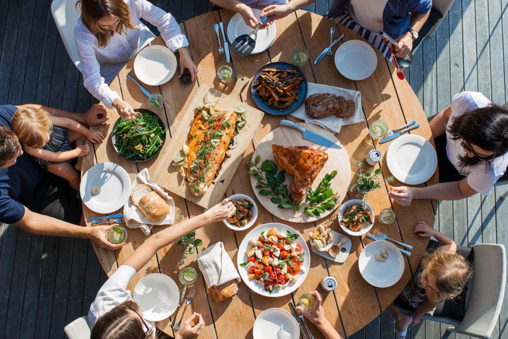 Runder Holztisch, gedeckt mit allerlei Köstlichkeiten