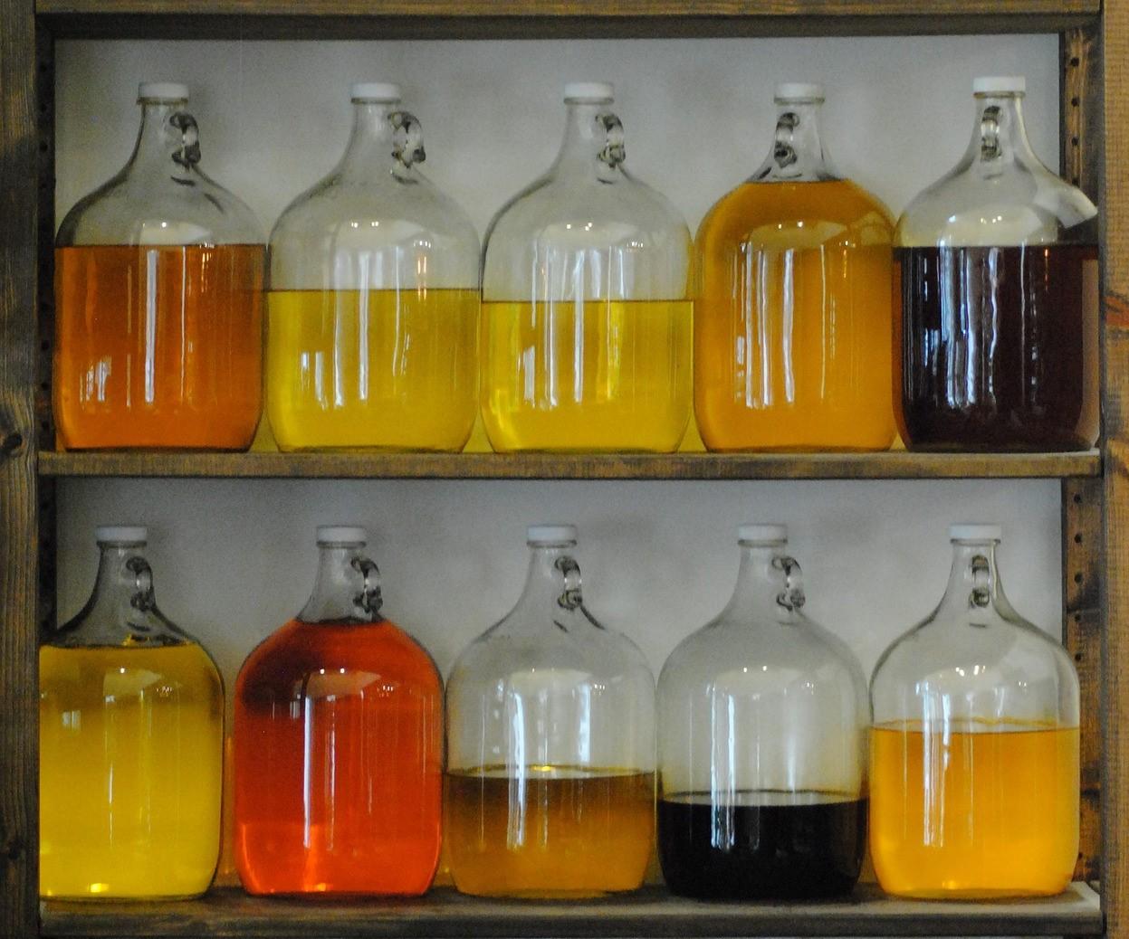 Große Flaschen befüllt mit verschiedenfärbigen Ölen in einem Regal
